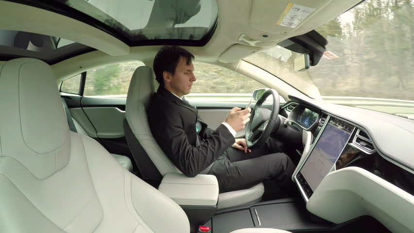 CLOSE UP: Young businessman texting writing messages on mobile phone while sitting behind self-driving steering wheel in autonomous autopilot driverless electric car traveling along countryside road