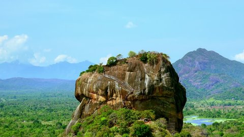 Tourists visiting famous Lion Rock fortress with ancient gardens world heritage in Sri Lanka. Aerial view on amazing landscape near Sigiriya. Zooming video