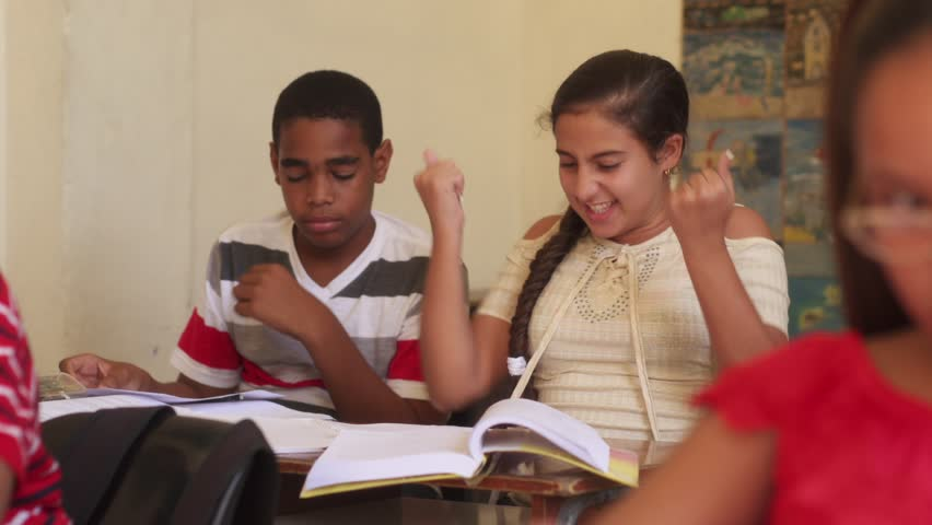 Young people and education. Group of hispanic students in class at school during lesson. Happy female student cheering for good grades on test, cheerful girl and joy
