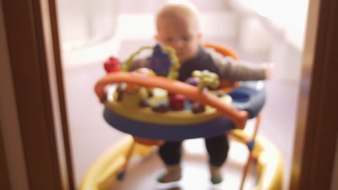 cute baby boy playing inside baby walker