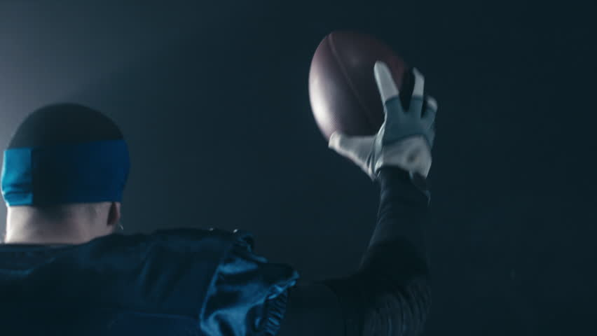 CU Caucasian male American football player rising a ball in his hand against dark background during the game. 4K UHD RAW edited footage #24535649