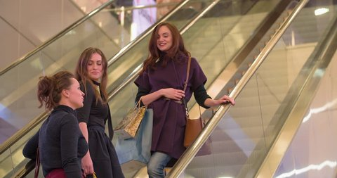 Happy women friends shopping at the mall 4K video. Girls with sale boxes moving on escalator. Female talk on moving stairs.
