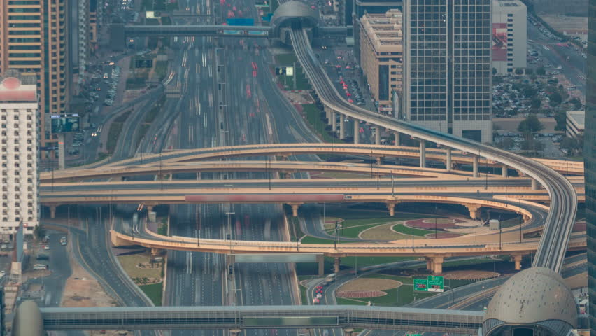 Aerial top view of highway junction with traffic timelapse in Dubai, UAE, at sunset. Famous Sheikh Zayed road in Dubai downtown. Transportation and driving concept view from rooftop.