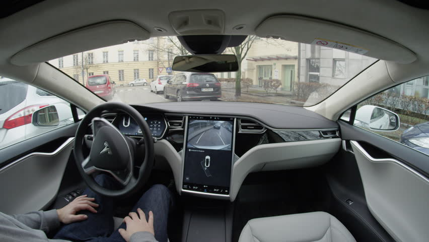 LJUBLJANA, SLOVENIA - FEBRUARY 4, 2017: Fully autonomous self-driving autopilot Tesla Model S driverless car entering a park seek mode and self-parking into space with no action required by the person