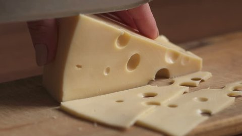 Process of cutting the cheese on a cutting board close-up, slow motion.