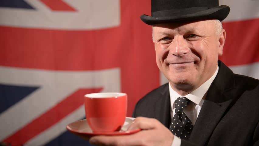 Smiling British businessman wearing traditional black bowler hat and matching suit, sipping/drinking tea then raises eyebrows in approval, stands against large Union Jack background in a light breeze.