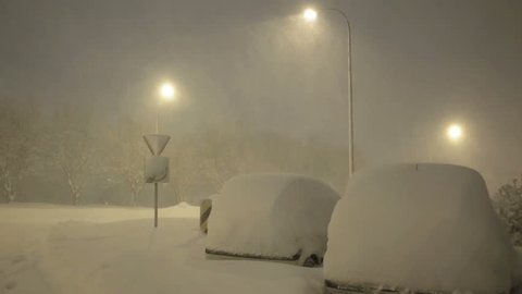 Cars under street lamps covered in deep snow winter blizzard Reykjavik Iceland