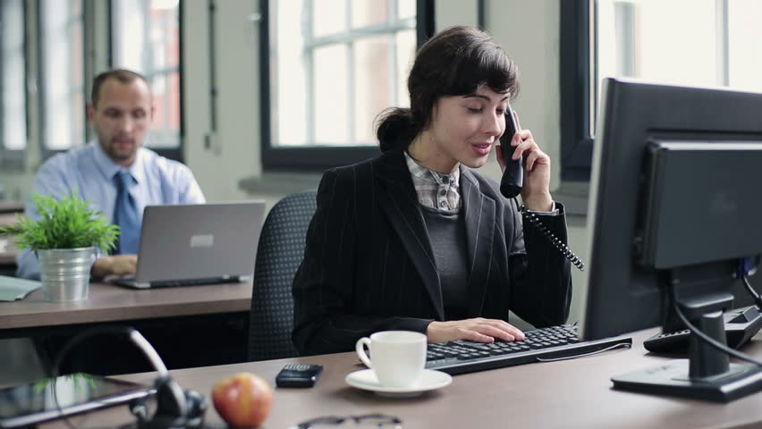 Young attractive businesswoman talking on telephone in the office