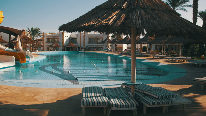 Sunny Hotel Resort with luxury blue swimming pool, Waterslides, palm trees, Beach Umbrellas and sunbeds in Egypt. Rich vacation on the sunny resort. Empty Egyptian hotel with swimming pool. Relax