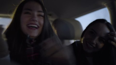 Fun Teen Girls Practice Funny Dance Moves Together In Back Seat Of Moving Car At Night