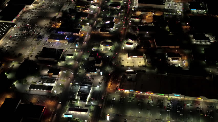 AERIAL HELI SHOT Flying above lit commercial zone with many grocery shops, malls, supermarkets, warehouses and other buildings at night. Big parking lots full of automobiles, vans, SUV parked in front