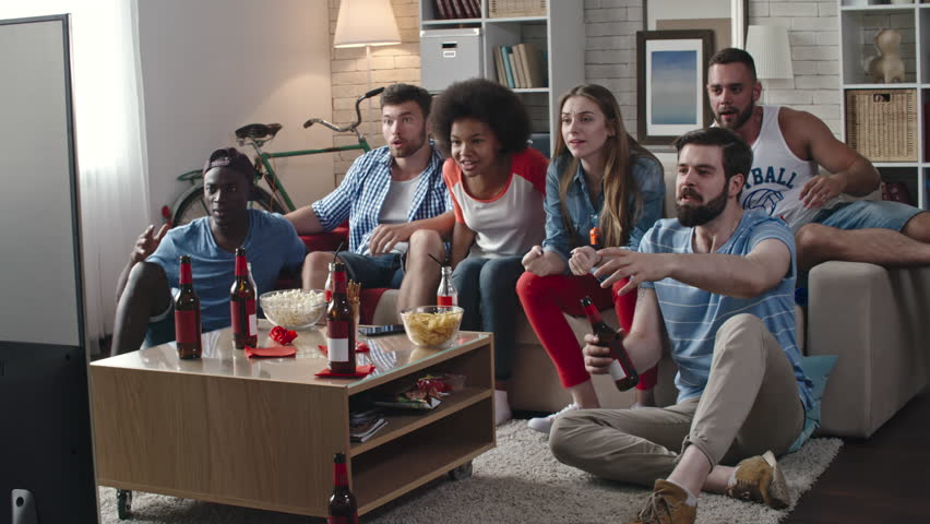 Zoom in of multi-ethnic group of friends celebrating victory of their team. They yelling, clapping hands and whistling while sitting in living room and watching TV match | Shutterstock HD Video #24648476