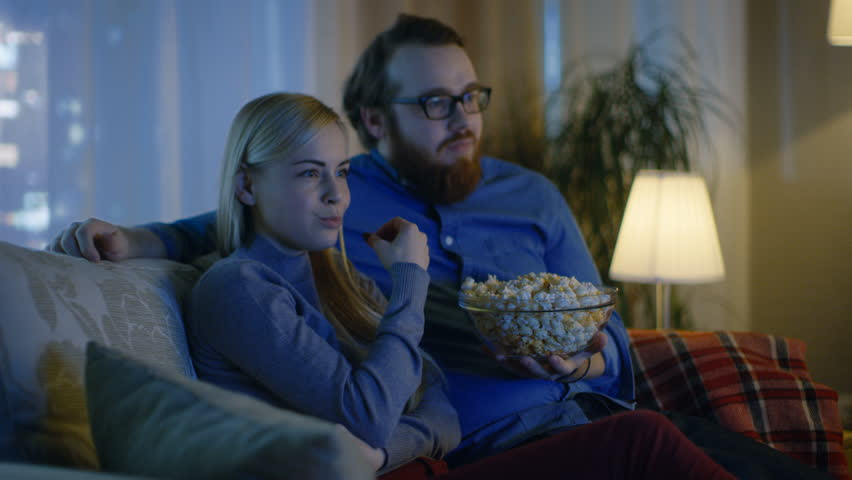Couple Watching TV. They Sit on a Sofa in Their Cozy Living Room and Eat Popcorn. It's Evening. Shot on RED EPIC-W 8K Helium Cinema Camera.