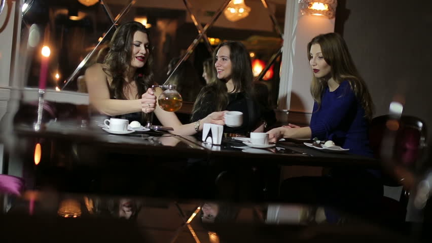 three girls drink tea and laughing in restaurant