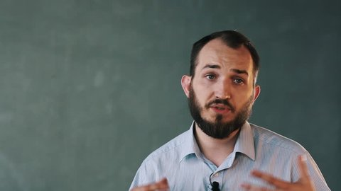 Young caucasian bearded businessman in striped shirt with lavalier microphone on isolated background wall give interview, gesturing a lot