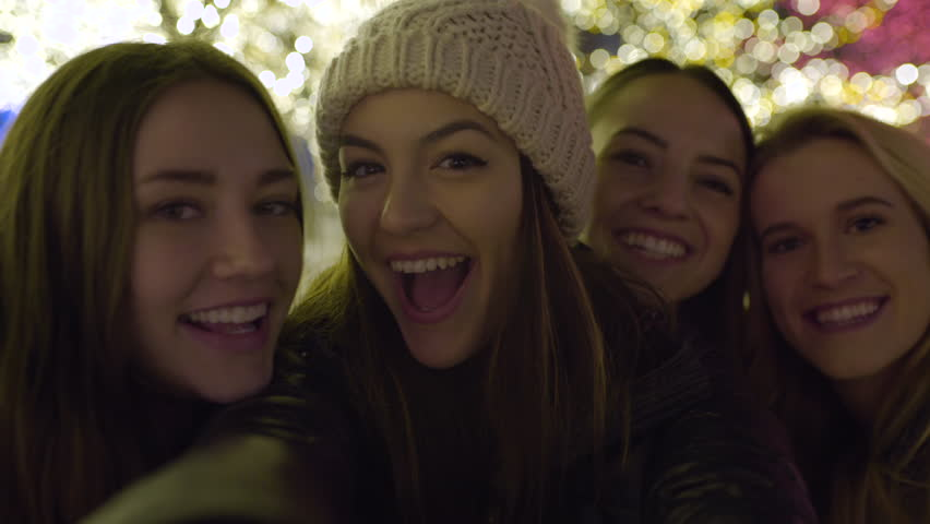 Group Of Fun Young Women Making Funny Faces And Smiling For Selfies At Night, Beautiful Christmas Lights In Background