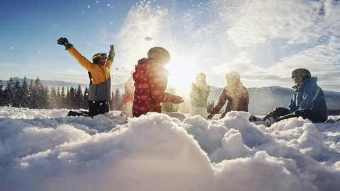 Happy group of skiers having fun sitting in snowdrift with snowboards and tossing snow