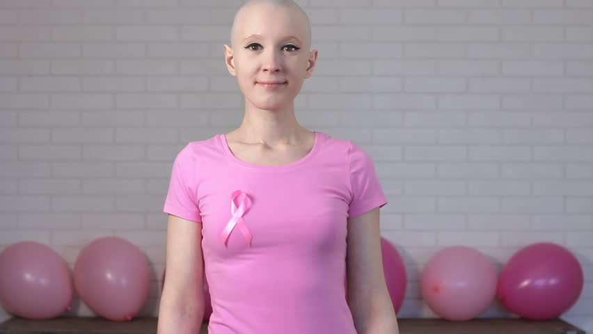 Happy breast cancer survivor woman pointing at breast cancer awareness ribbon - breast cancer awareness concept