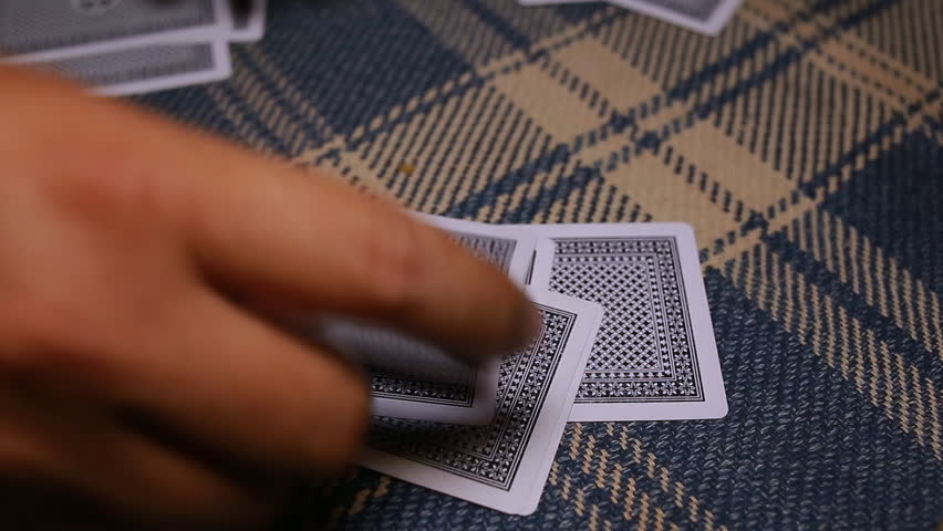 Close up of hands holding black deck of playing cards.