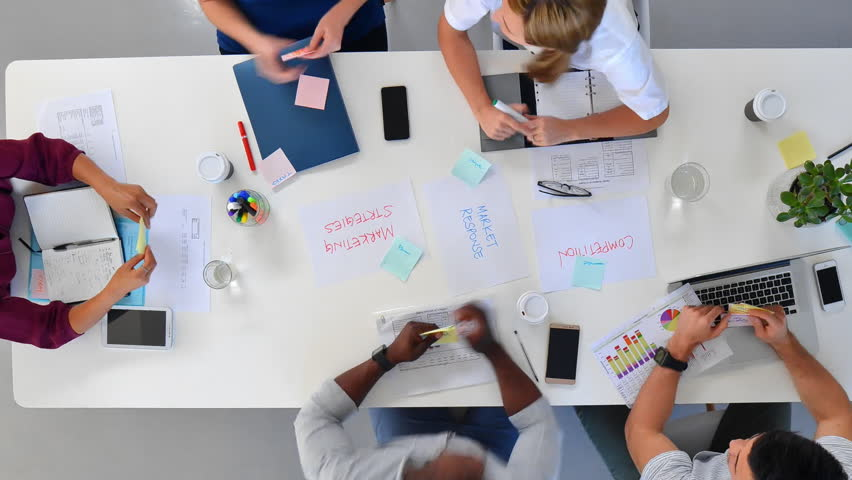 Multi-ethnic diverse business team meeting brainstorming teamwork across boardroom table overhead angle timelapse | Shutterstock HD Video #24713675