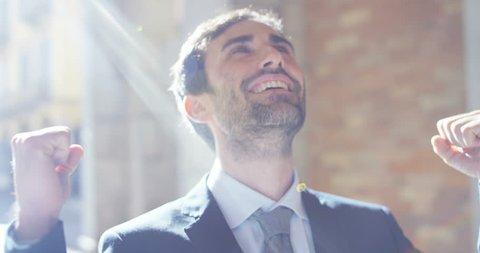 A businessman after a working visit to exult phone to have received a promotion or winning a bet. Concept: finance, business, exultation, victory, bet, working career,aspiration