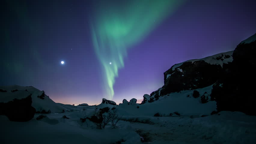 Aurora borealis moving over snow covered volcanic terrain Reykjavik Iceland