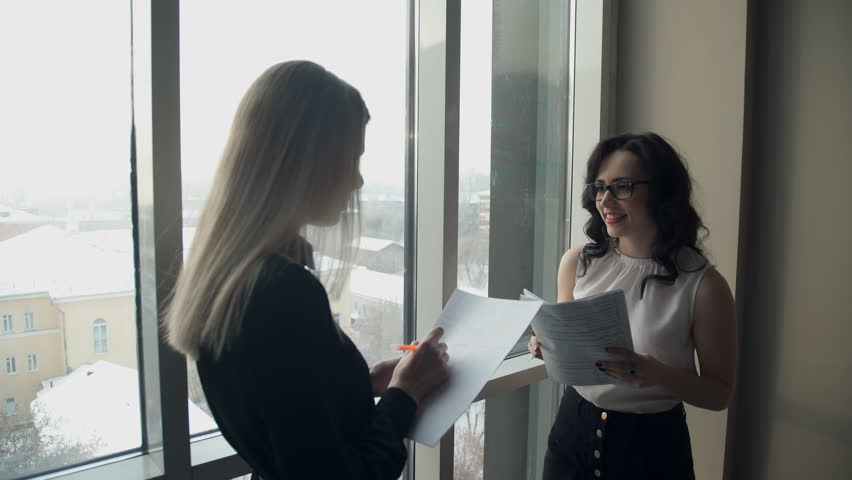 Two business women against window in hall discuss topics. tall blonde woman with straight hair holding folder with paper, pen, listening to employee, says, writes important points in synopsis in hall. | Shutterstock HD Video #24777845
