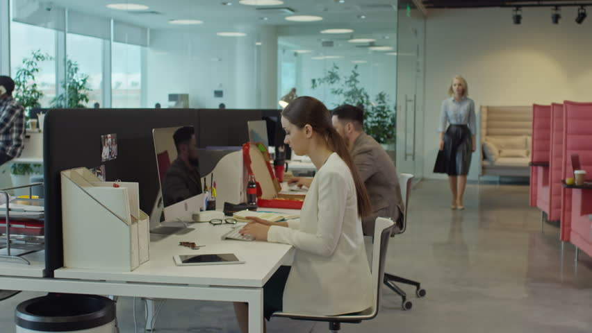 Tracking shot of office workers using computers; businessman sitting on couch in lounge area and talking with African woman; young man talking on the phone in the background | Shutterstock HD Video #24788000