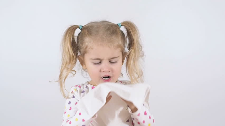 Little Girl with a runny nose. Blowing his nose with disposable tissues isolated on a white background