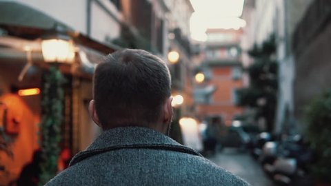 Young tourist man walking up the small street with cafe. Stylish guy spending vacation in Europe, exploring old town.