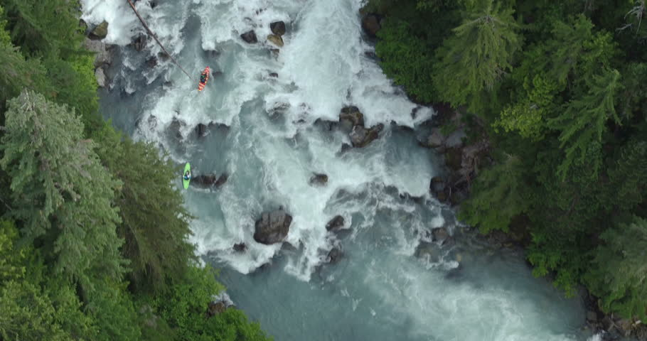 Aerial - Two kayakers paddling down blue river waterfall rapids with trees - Pacific Northwest BC