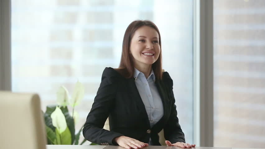 Young happy beautiful businesswoman wearing formal suit meeting casual client at modern office. Negotiations and work with documents between colleagues or partners. Young man choosing consultant | Shutterstock HD Video #24858752