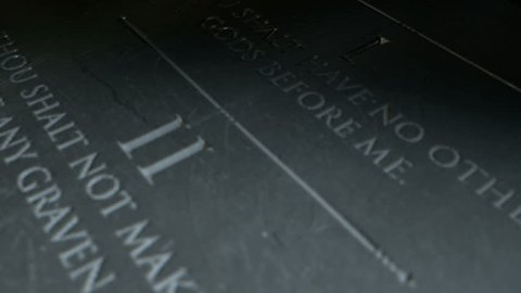 A slow close up pan across a stone tablet with the second five of the ten commandments inscribed onto them