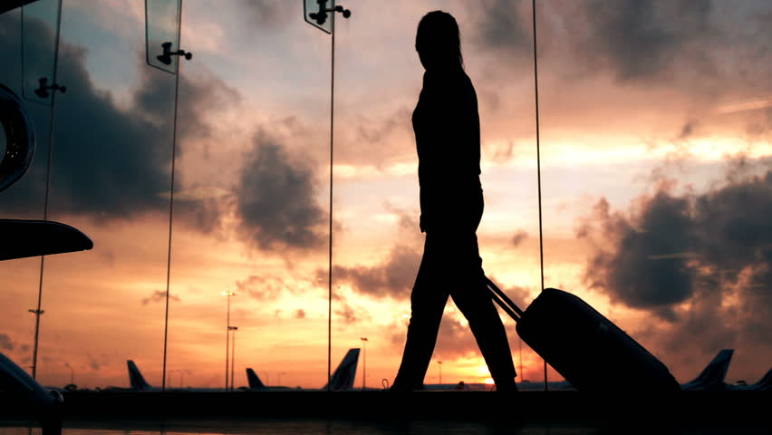 Silhouette of woman with suitcase walking through hall at airport, super slow motion 240fps  | Shutterstock HD Video #24864329