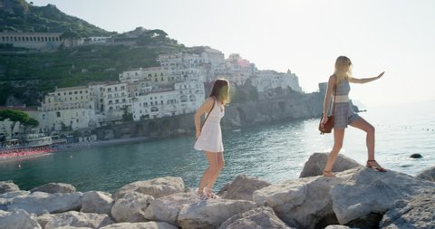 Tourist women balancing on rocks walking along beach best friends hanging out travel girls exploring European travel adventure summer vacation Amalfi Coast Italy