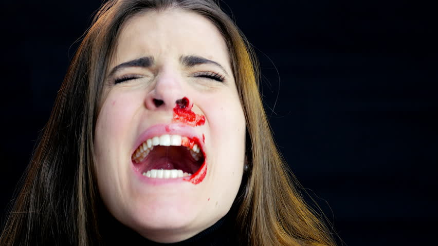 Young woman screaming after domestic violence bleeding from nose