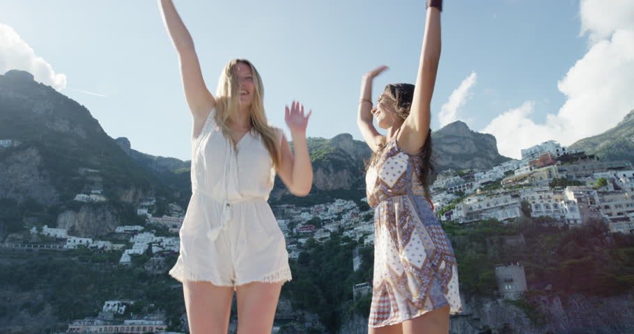 Woman dancing on boat at sunset girl friends doing silly freestyle dance on yacht enjoying nature celebrating European summer holiday travel vacation adventure in Positano Amalfi Coast Italy