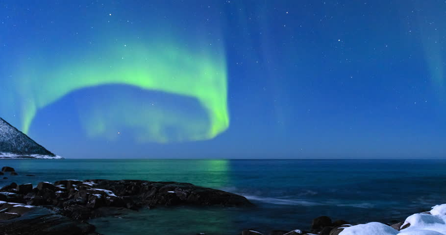 Northern Lights, polar light or Aurora Borealis in the night sky over Senja island in Northern Norway. Snowy mountains in the background with the Norwegian Sea reflecting the lights in the foreground.