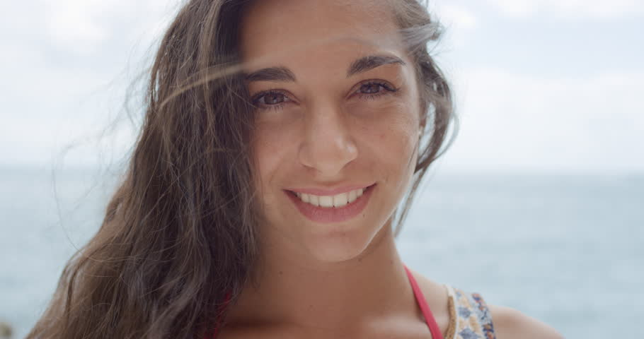 Close up portrait of Beautiful Young Woman smiling hair blowing in wind on tropical beach slow motion
