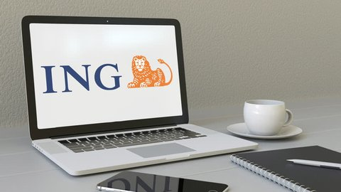 Opening laptop with ING Group logo on the screen. Modern workplace conceptual editorial 4K clip