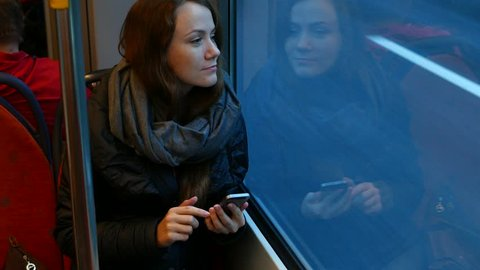 Young adult woman ride in tram at evening time, look to window with faint smile. She hold smartphone, watch message and touch screen. Pleasant fatigue after walking at city, pensive and positive mood