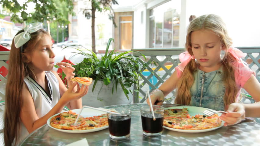 Two little girls eating pizza in a fast food restaurant outdoors