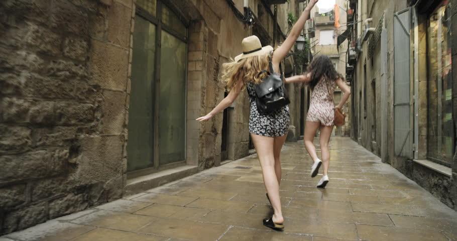 Best friends dancing in street in rain silly dance in rainy weather celebrating adventure Barcelona Spain | Shutterstock HD Video #24945005