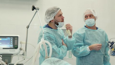 Mature surgeon pointing his hand on monitor with green chroma key. Senior doctor showing his younger bearded colleague something at the screen. Caucasian medical specialist agreeing with his older