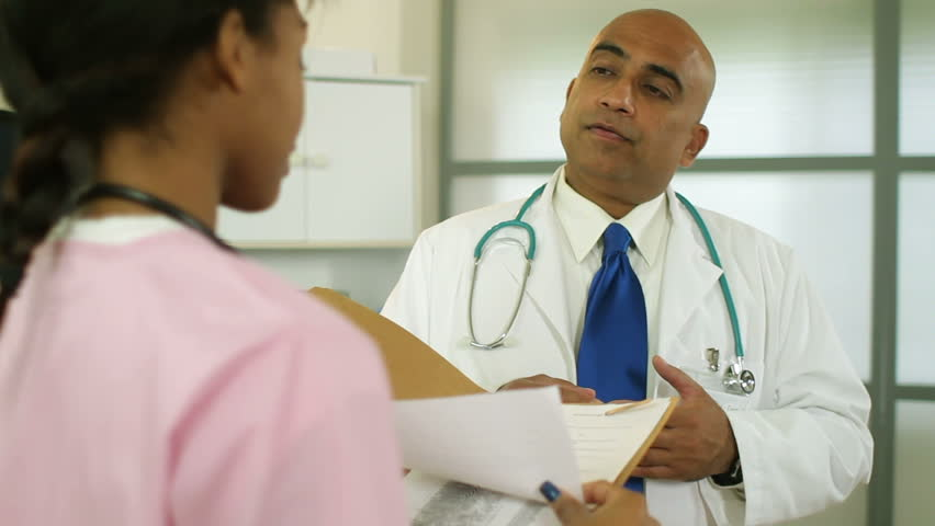 Doctor talking to nurse chuckles at something he finds amusing in their conversation. | Shutterstock HD Video #2495375