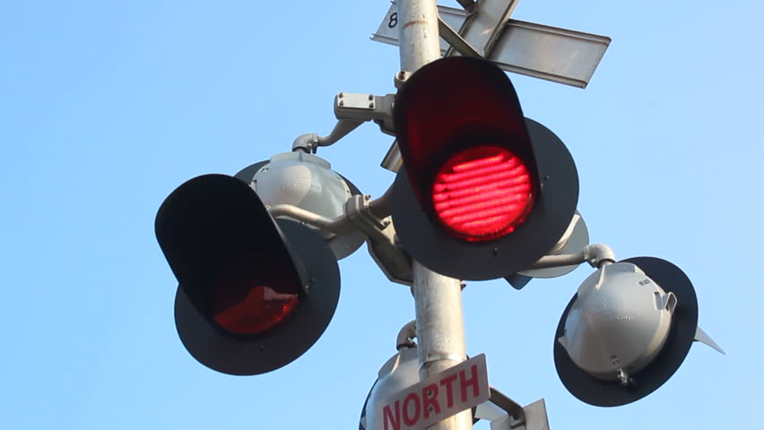 Flashing lights warn that a train is approaching./Flashing Railway Crossing Lights/Flashing lights warn that a train is approaching.