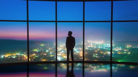 The man stand near the panoramic window on the night city background. Time lapse