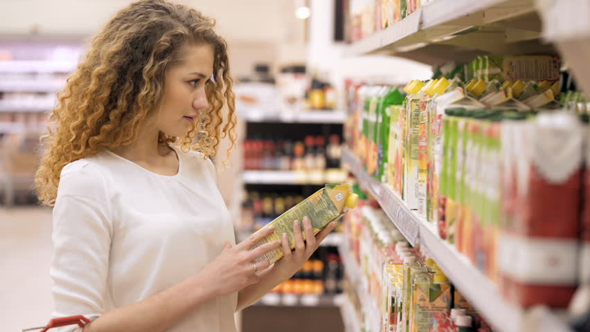 Woman chooses juice in the supermarket. Woman Choosing Products in Shopping Mall. Girl stands near the store shelf and selects the products | Shutterstock HD Video #25025138