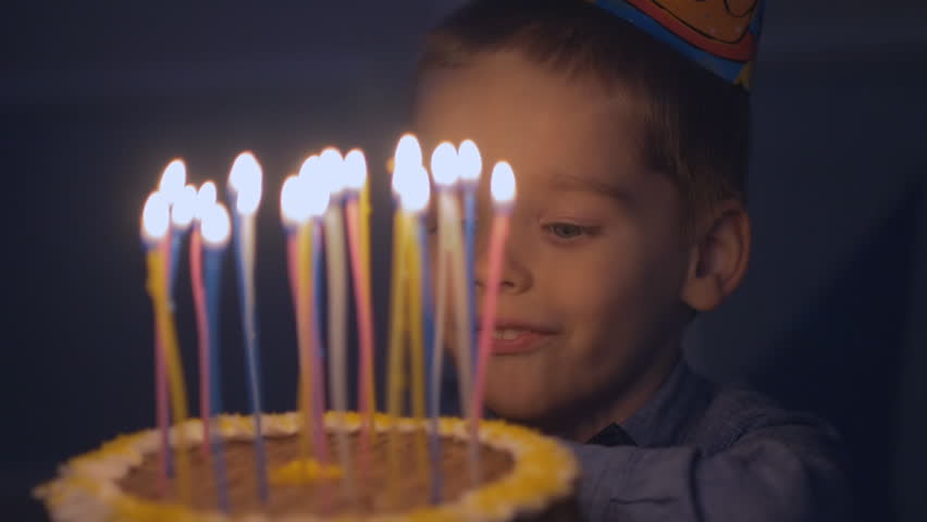 Little Boy Looks At The Candles On A Birthday Cake And Smiles In Slow Motion