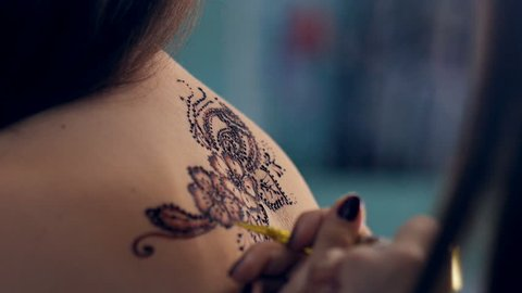 8f254dd78baf2 Artist applying henna tattoo on women back. Mehndi is traditional Indian  decorative art.
